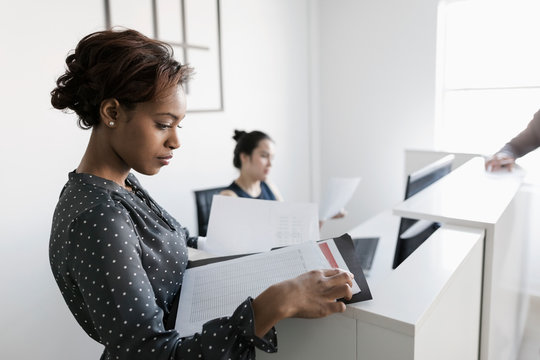 Businesswoman reading paperwork at reception desk in office