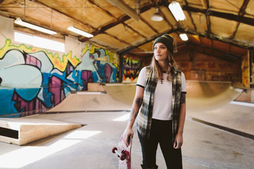 Portrait confident young female skateboarder at indoor skate park