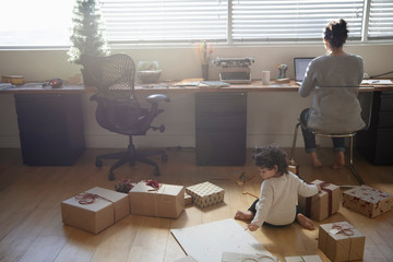 Toddler girl playing with Christmas gifts on floor behind mother working at laptop