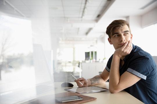 Thoughtful businessman with digital tablet looking over shoulder