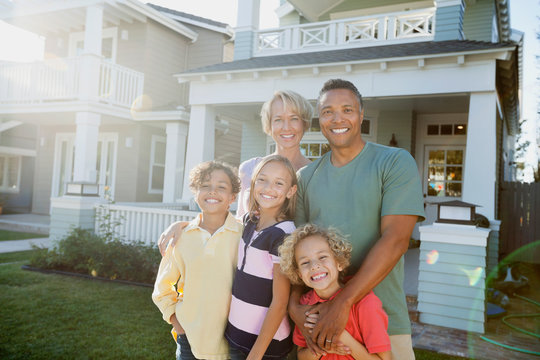 Portrait of happy family standing outside home