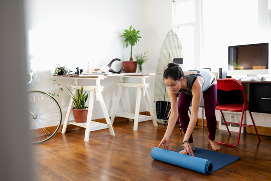 Young Latinx woman unrolling yoga mat in apartment