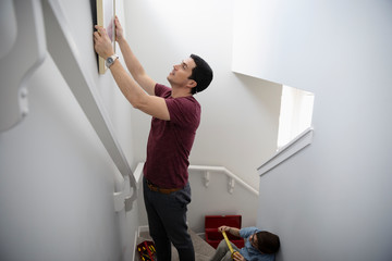 Man hanging picture frame on wall above stairs