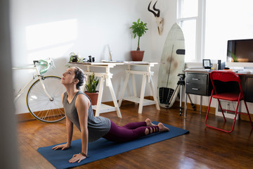 Young Latinx woman practicing yoga upward facing dog pose in apartment