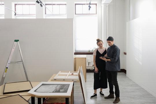 Art gallery owners using digital tablet
