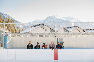 Friends standing at outdoor ice hockey sideline below mountains