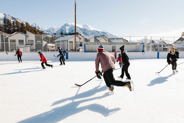 Community playing outdoor ice hockey with mountains in background