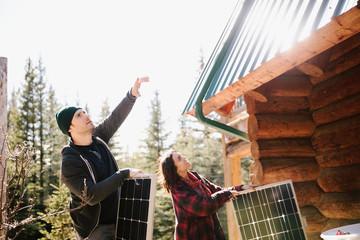 Couple installing solar panels on cabin