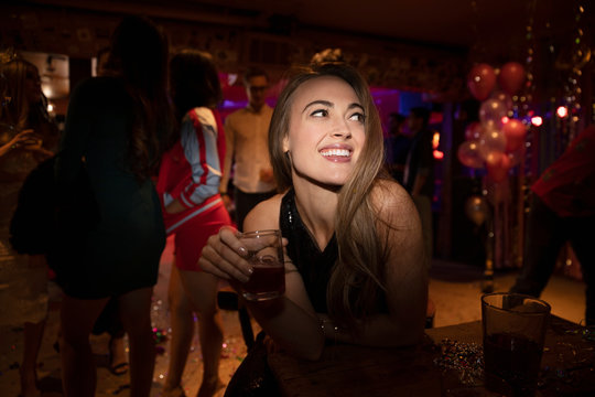 Smiling confident young woman drinking cocktail in nightclub