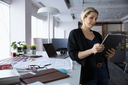 Female interior designer using digital tablet in design studio