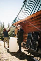 Couple installing solar panels and rain barrel on cabin