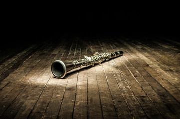 a black woodwind clarinet lies on a dark brown wooden stage in the rays of light Fotobehang