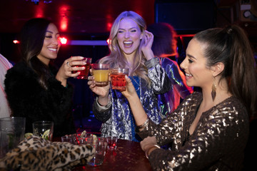 Young women friends toasting cocktails in nightclub