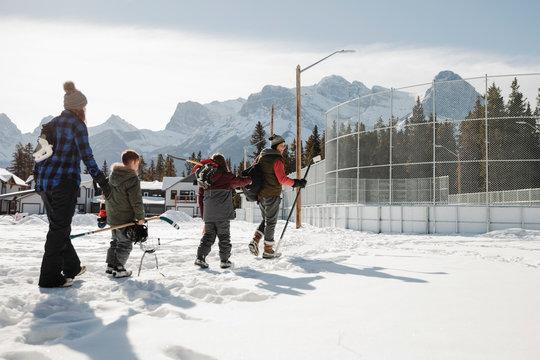 Family walking toward outdoor ice hockey rink