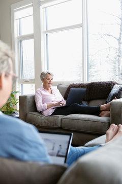 Senior women using laptops on living room sofas