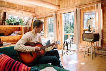 Man with dog playing guitar in cabin