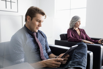 Businessman using digital tablet in office lobby