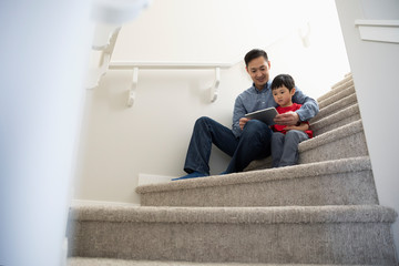Father and son using digital tablet on stairs Fotomurales