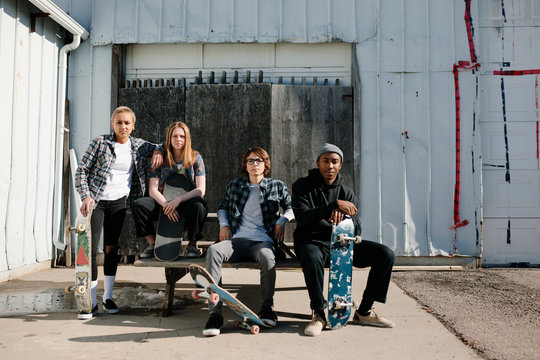 Portrait confident, cool young skateboarder friends in sunny parking lot