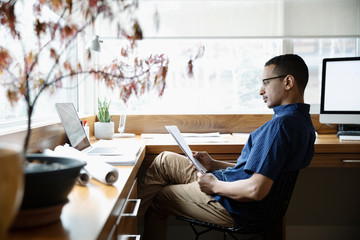 Focused male architect working from home, reading paperwork in home office