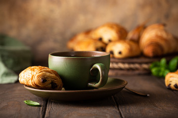 Green cup of tea with mini chocolate bun, puff pastry on old wooden table. Tasty tea break concept, copy space.