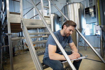 Male brewer with clipboard working in brewhouse distillery