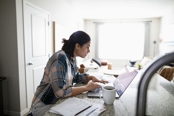 Woman working from home at laptop in kitchen