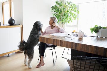 Senior woman with dog talking on smart phone