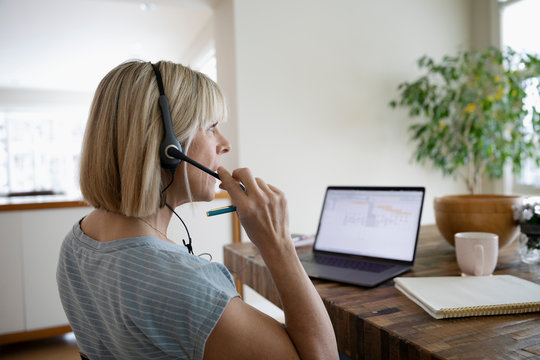 Woman with headset working from home, using laptop at dining table