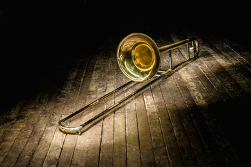 golden brass instrument trombone lies on a dark brown wooden stage in the rays of light.