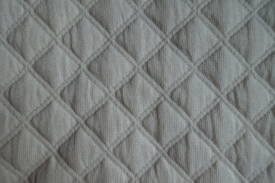 Diamonds pattern on white quilted fabric from above