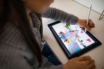 Girl drawing on digital photo with stylus on digital tablet