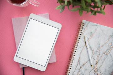 Digital tablet and notebook on pink background