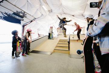 Friends skateboarding at indoor skate park