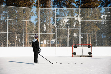 Woman playing outdoor ice hockey, practicing penalty shots
