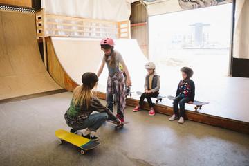 Kids learning how to skateboard at indoor skate park