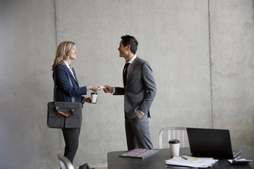 Business people networking, exchanging business cards in meeting