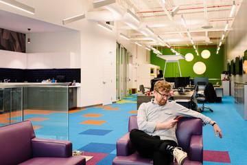 Creative businessman using smart phone in open plan office Fotobehang