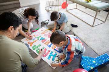 Family coloring birthday sign on floor