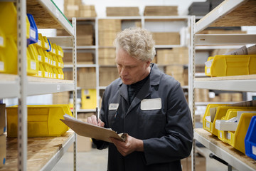 Male worker checking inventory in warehouse