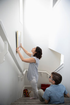 Son watching mother hang picture on wall above stairs