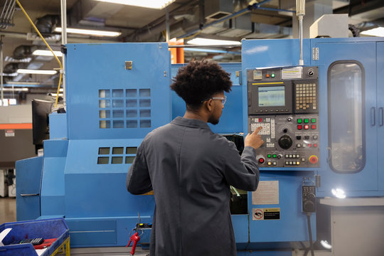 Male machinist operating machinery in factory