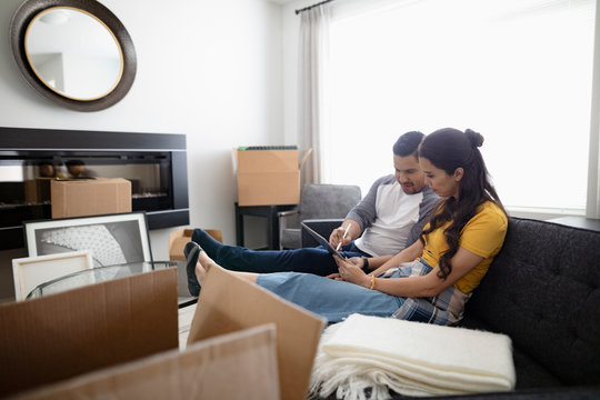 Couple taking a break from moving, using digital tablet on living room sofa