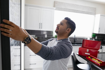 Man hanging picture frame on kitchen wall