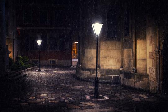 Rainy night in old European city with lanterns