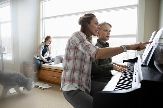 Mother helping son practicing piano while daughter does homework in background