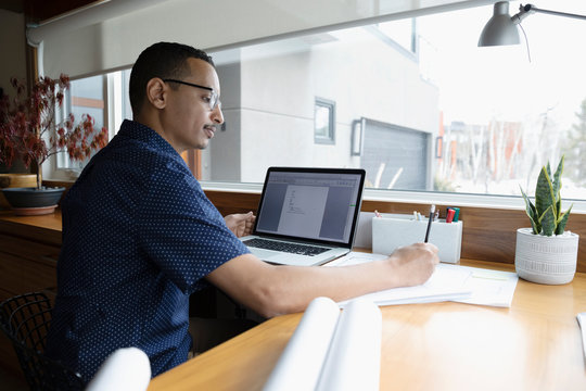 Male architect working from home, using laptop in home office