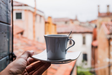 cropped view of woman holding cup of coffee in Venice, Italy