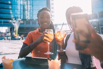 two women sisters sitting outdoor taking selfie