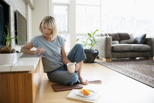 Woman working from home, using digital tablet on living room floor